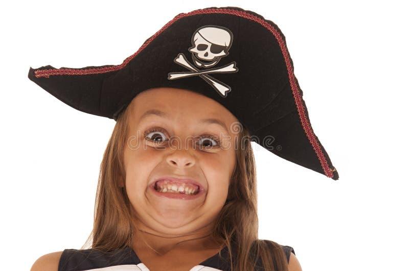 Jong meisje in de hoed die van de piraat een zeer grappig gezicht trekken stock foto
