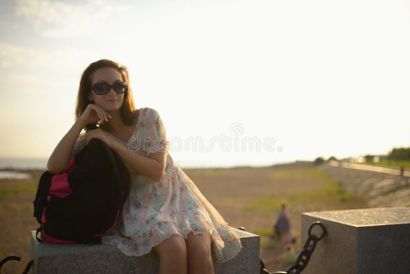 Jong meisje de reiziger in een kleding en een rugzak stock fotografie