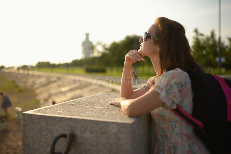 Jong meisje de reiziger in een kleding en een rugzak stock afbeeldingen