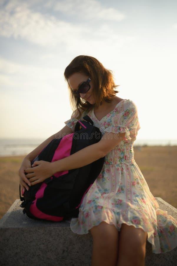 Jong meisje de reiziger in een kleding en een rugzak royalty-vrije stock afbeelding