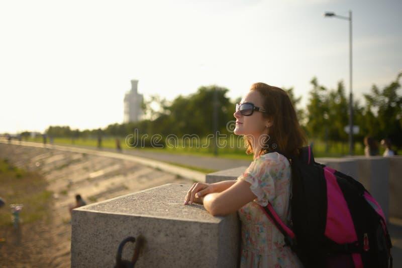 Jong meisje de reiziger in een kleding en een rugzak royalty-vrije stock afbeeldingen