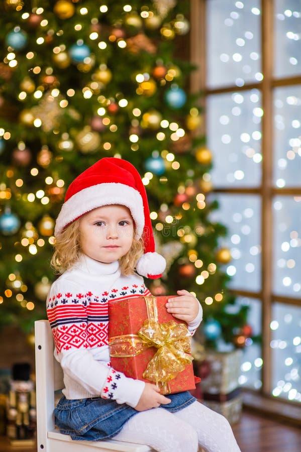 Jong meisje in de rode zitting van de santahoed met grote giftdoos dichtbij C stock fotografie