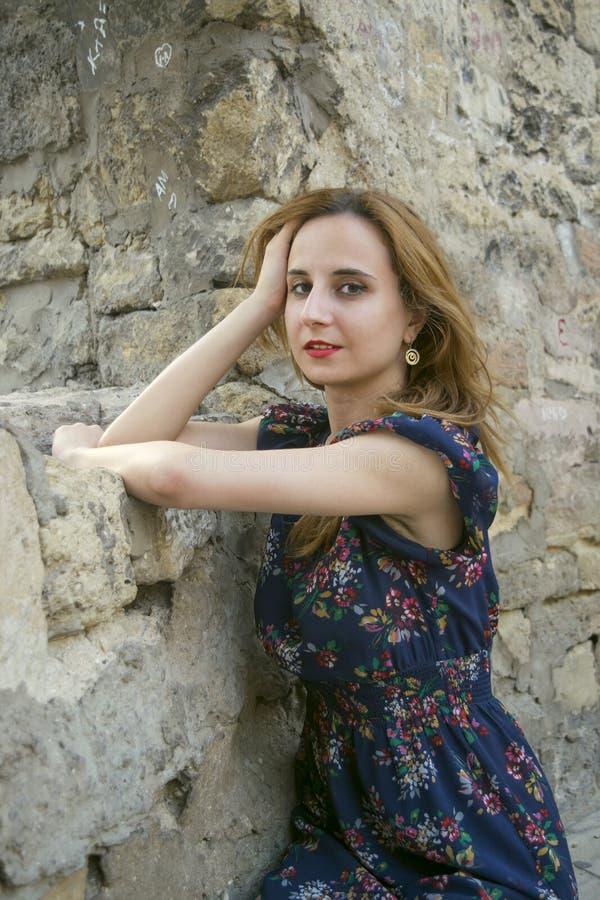 Jong meisje dichtbij een steenmuur royalty-vrije stock fotografie