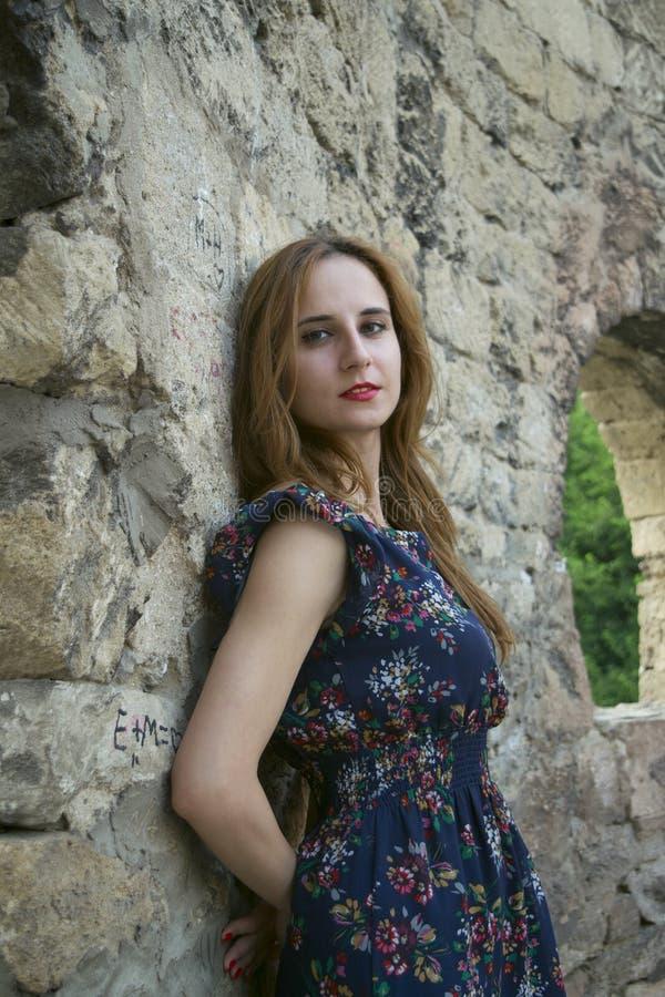 Jong meisje dichtbij een steenmuur royalty-vrije stock afbeelding