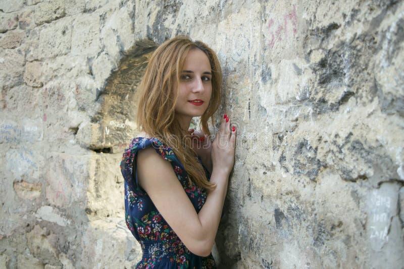 Jong meisje dichtbij een steenmuur stock afbeeldingen