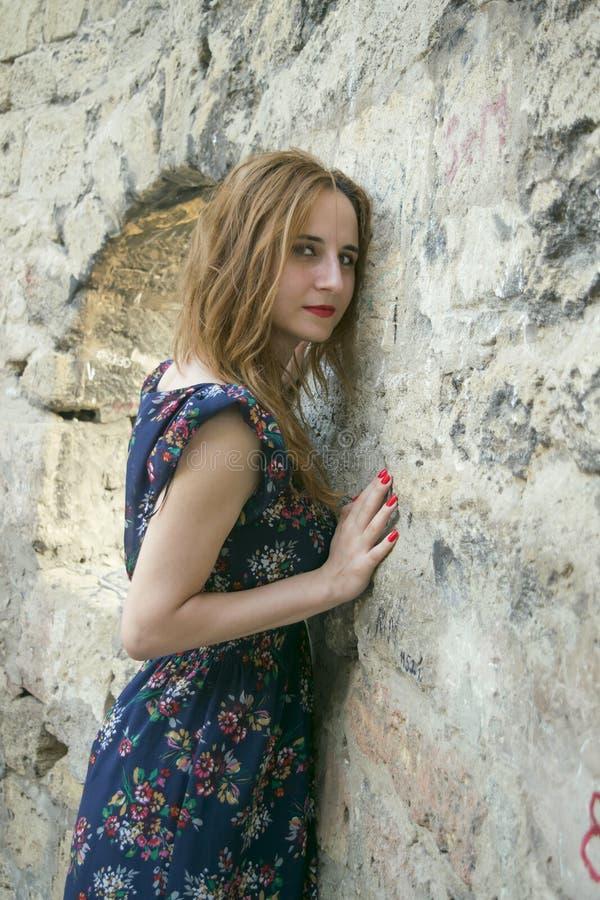 Jong meisje dichtbij een steenmuur royalty-vrije stock afbeeldingen