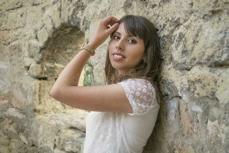 Jong meisje dichtbij een steenmuur stock foto