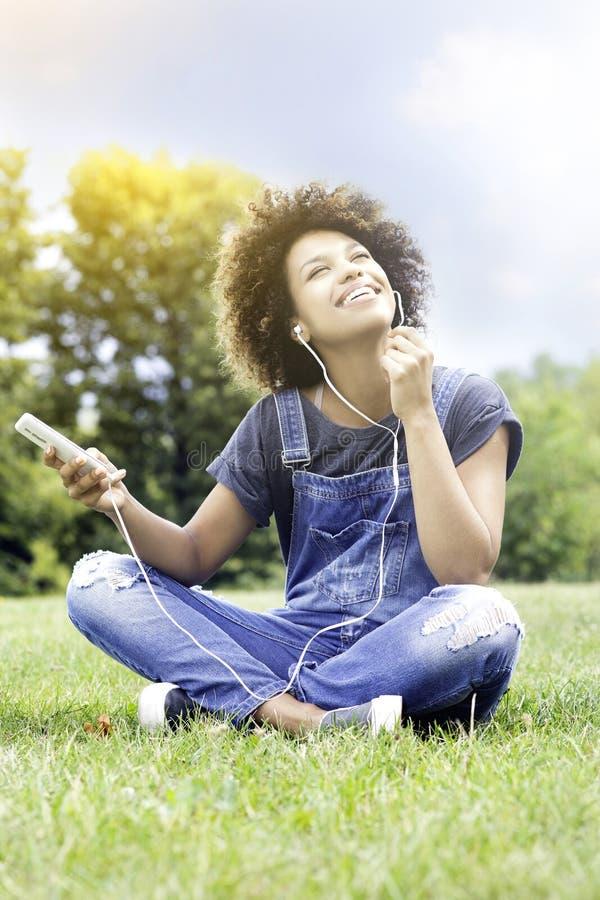 Jong meisje die aan muziek in park luisteren, het ontspannen royalty-vrije stock afbeeldingen