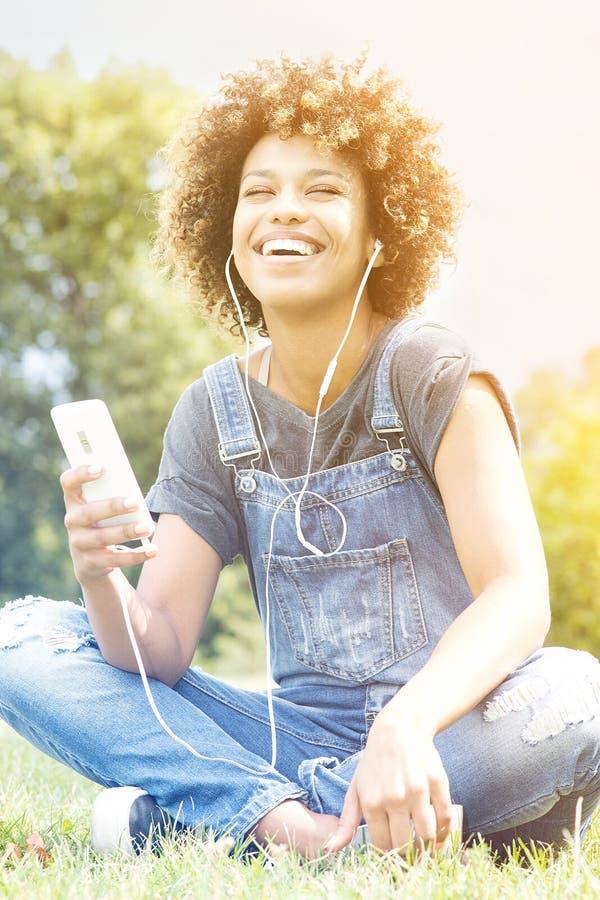 Jong meisje die aan muziek in park luisteren, het ontspannen stock afbeelding