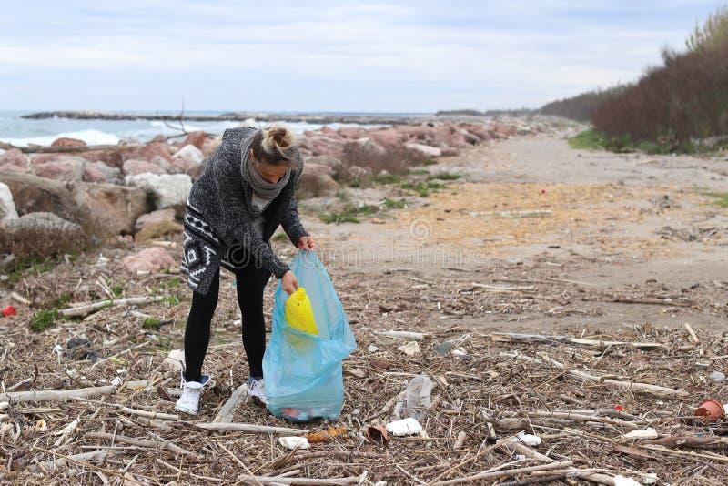 Jong Meisje die Afval van het Strand opnemen stock foto