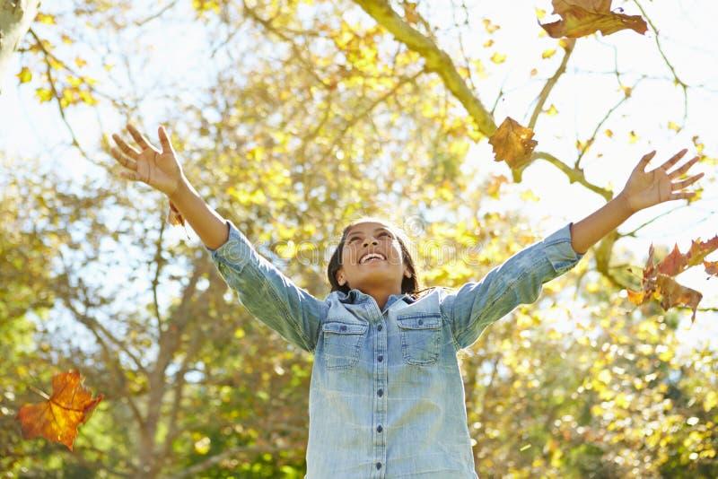 Jong Meisje die Autumn Leaves In The Air werpen stock foto's