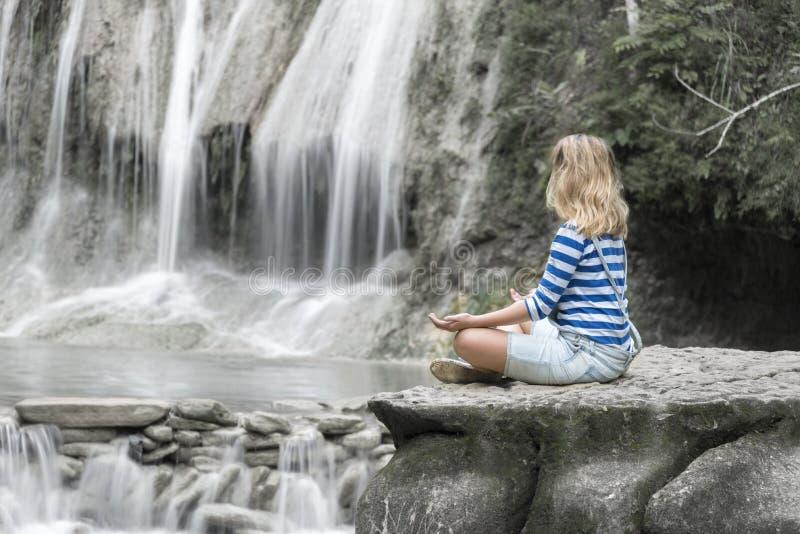 Jong meisje die bij de waterval mediteren royalty-vrije stock afbeeldingen