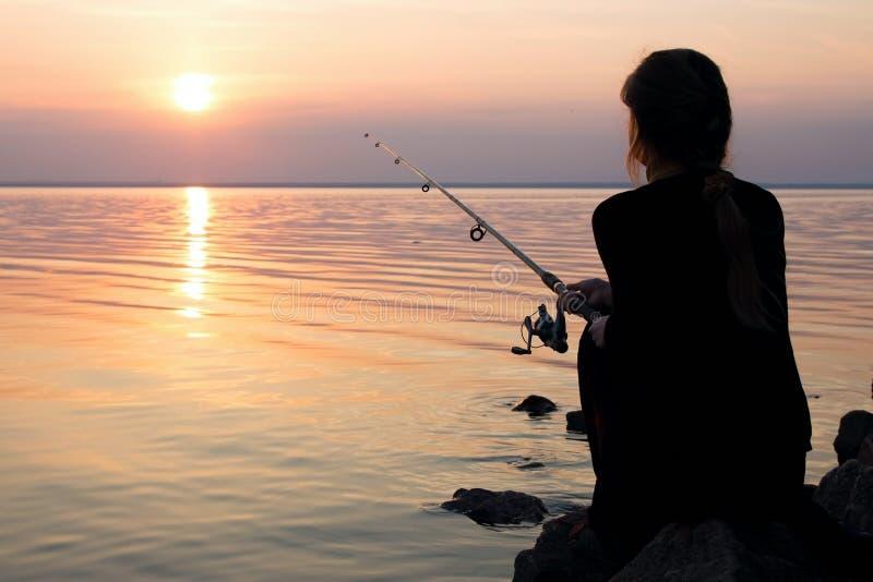 Jong meisje die bij zonsondergang dichtbij het overzees vissen royalty-vrije stock foto