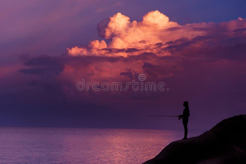 Jong meisje die bij zonsondergang vissen stock foto