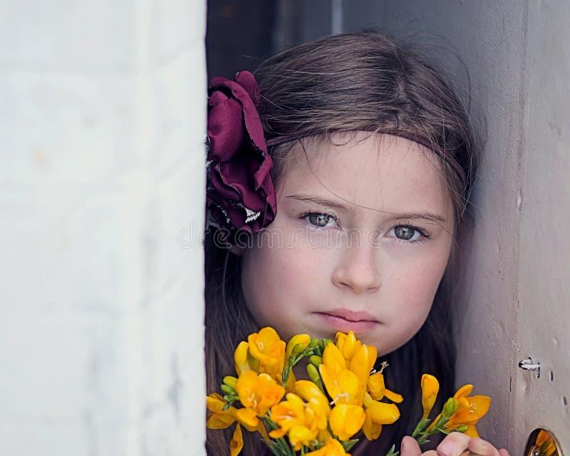 Jong Meisje die in Camera, Holdingsbloemen, tussen Witte Muren staren stock afbeelding
