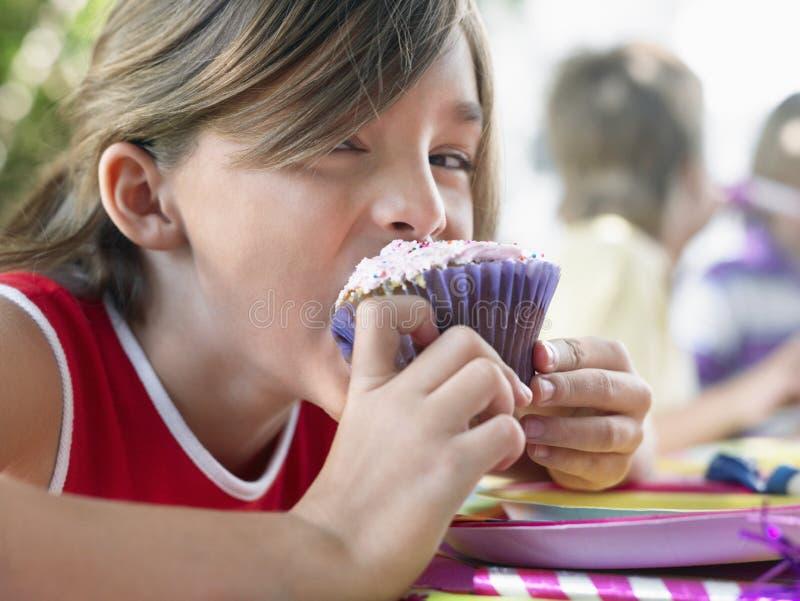 Jong Meisje die Cupcake eten bij Verjaardagspartij royalty-vrije stock foto