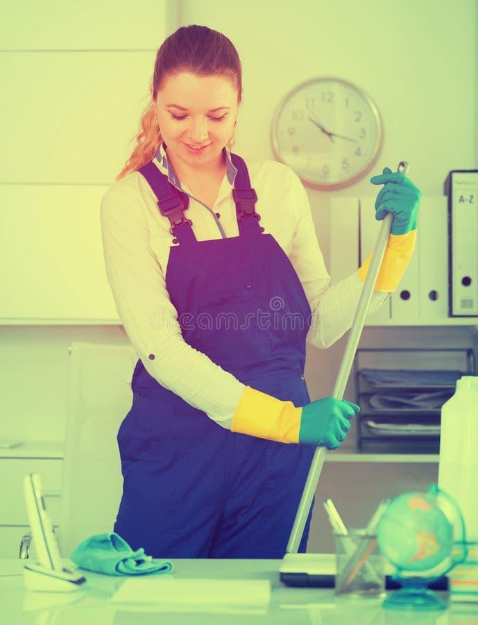 Jong meisje die de ruimte met zwabber schoonmaken royalty-vrije stock foto