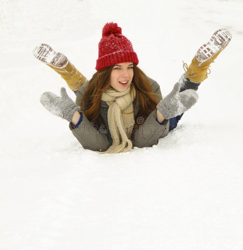 Jong meisje die in de sneeuw en de lach liggen stock foto