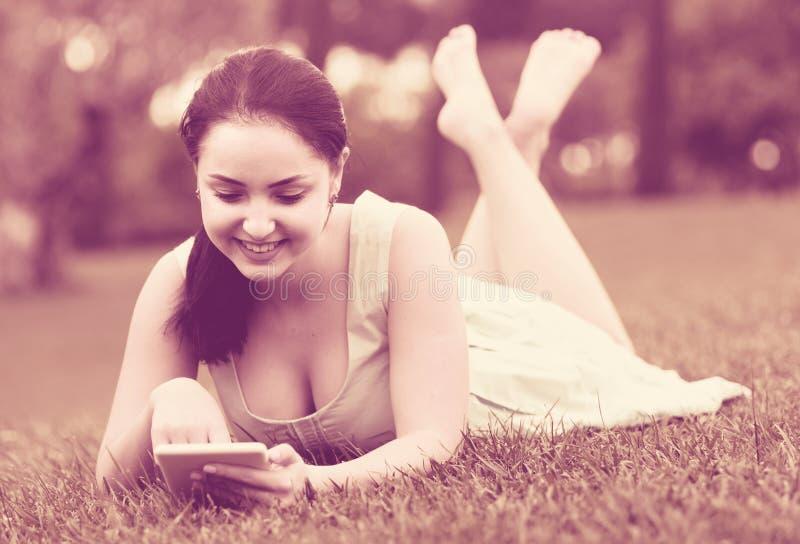 Jong meisje die digitale tablet gebruiken terwijl het liggen in groene de lentegeep stock afbeeldingen