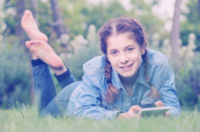 Jong meisje die digitale tablet gebruiken terwijl het liggen in groene de lentegeep royalty-vrije stock afbeeldingen