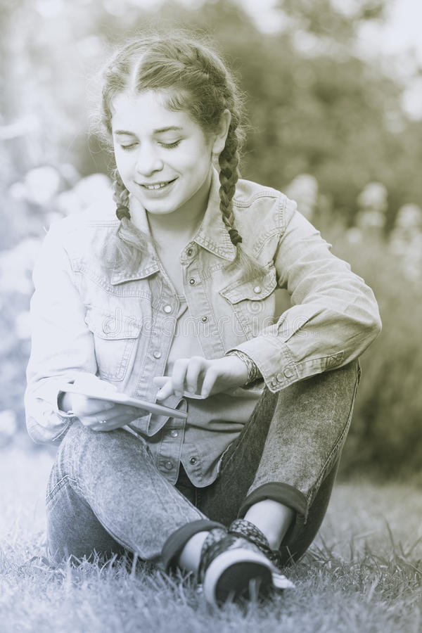 Jong meisje die digitale tablet gebruiken terwijl het liggen in groene de lentegeep royalty-vrije stock afbeelding