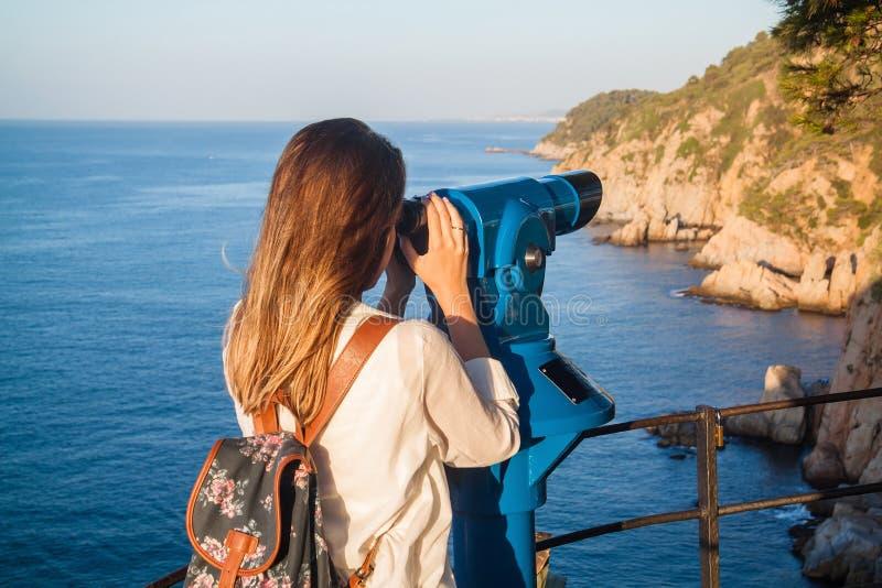 Jong meisje die door een muntstuk in werking gestelde verrekijkers kijken stock afbeeldingen