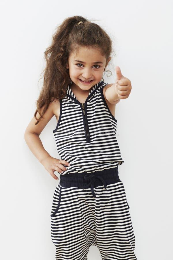 Jong meisje die duimen opgeven, het glimlachen royalty-vrije stock foto's