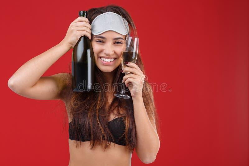 Jong meisje die een fles en een glas champagne houden stock afbeeldingen