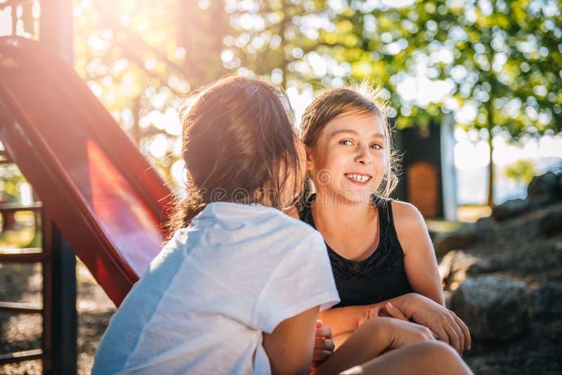 Jong meisje die een geheim fluisteren aan een ander meisje stock afbeeldingen