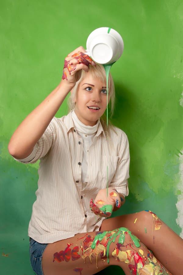 Jong meisje die een groene verf op zich van een kop gieten stock fotografie