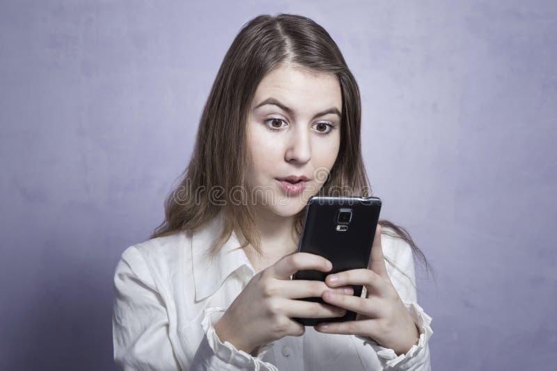 Jong meisje die een smartphone gebruiken stock afbeelding