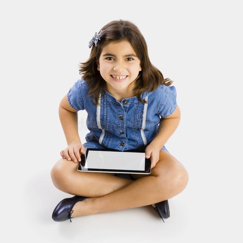 Jong meisje die een tablet gebruiken stock afbeelding