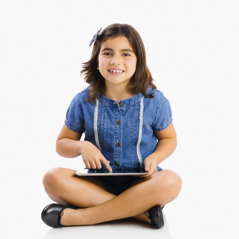 Jong meisje die een tablet gebruiken stock fotografie