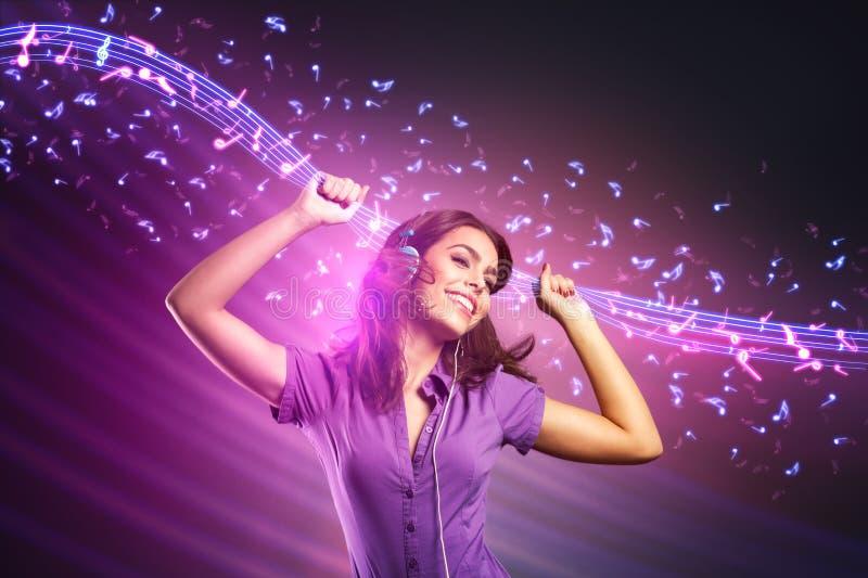 Jong meisje die en het luisteren muziek dansen stock foto