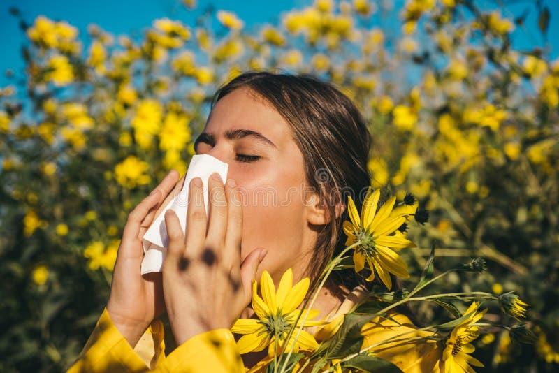 Jong meisje die en papieren zakdoekje in één hand en bloemboeket in andere houden niezen Jonge vrouw geworden neusallergie, griep royalty-vrije stock foto