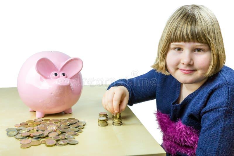 Jong meisje die euro muntstukken van spaarvarken tellen stock foto
