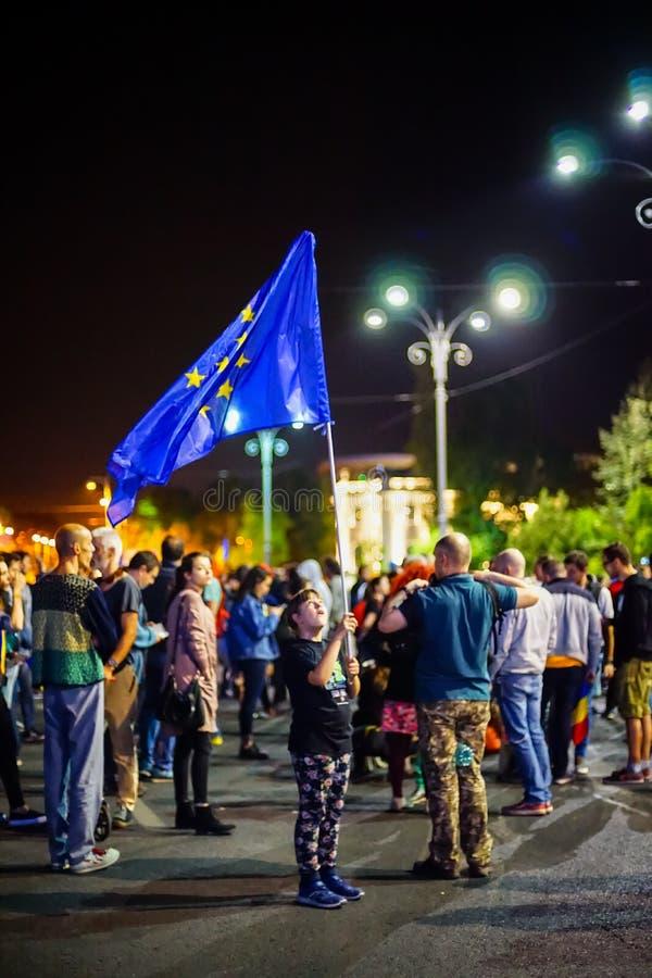 Jong meisje die Europese Unie vlag in Boekarest, Roemenië golven stock fotografie