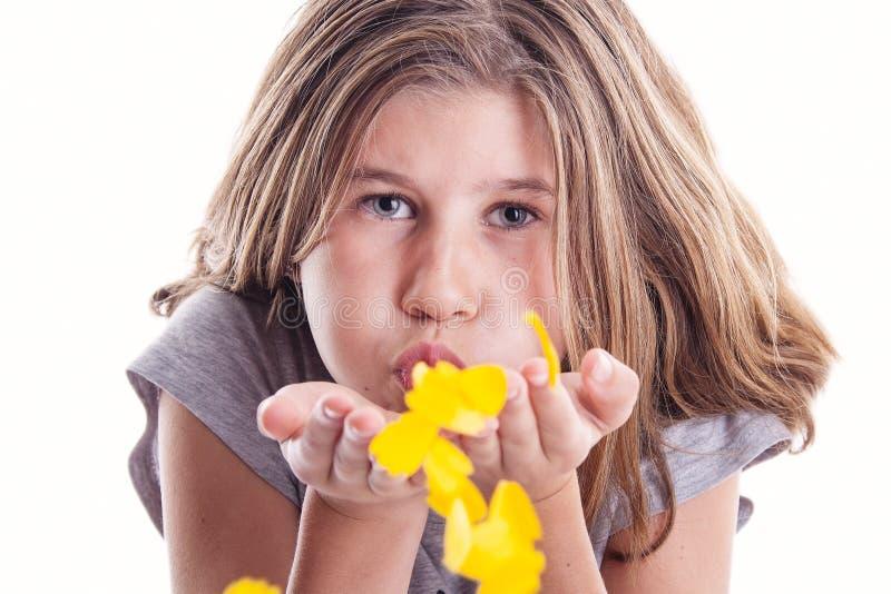 Jong meisje die gele bloemblaadjes in liefde blazen stock fotografie