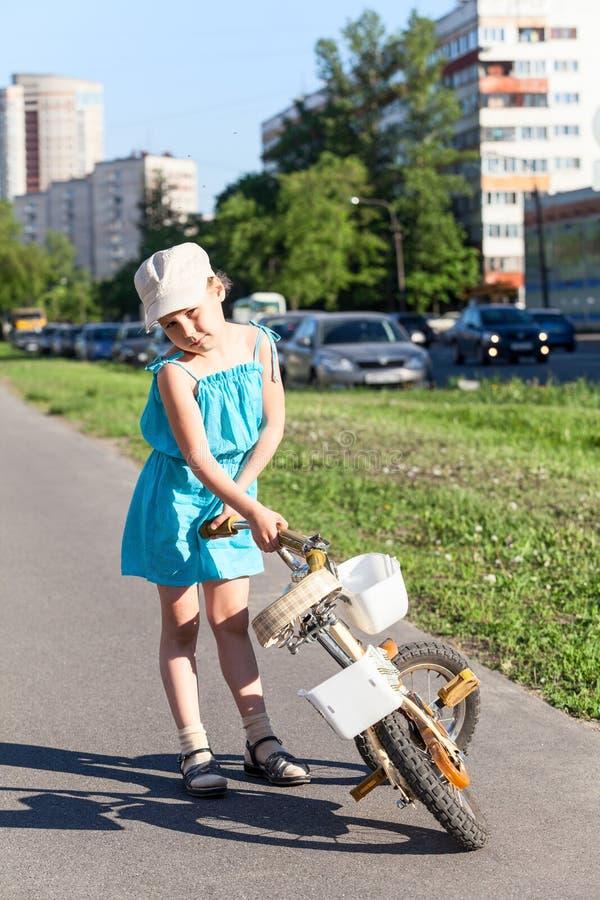 Jong meisje die haar fiets houden royalty-vrije stock afbeelding