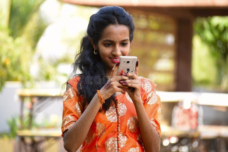 Jong meisje die haar mobiel, Pune bekijken royalty-vrije stock fotografie