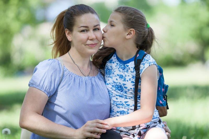 Jong meisje die haar moeder kussen terwijl het zitten op knieën, de zomer zonnig park, twee mensen stock afbeeldingen