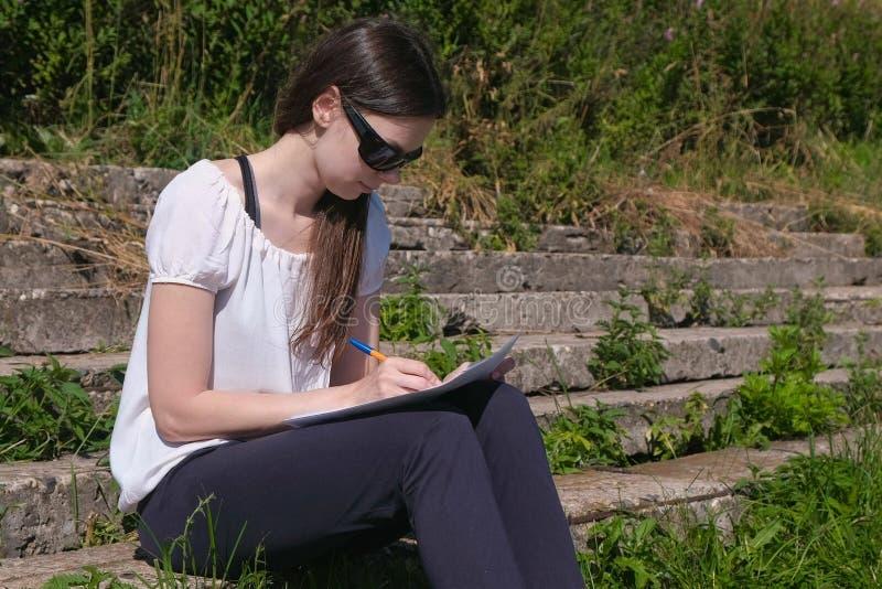 Jong meisje die haar taken en thuiswerkzitting in park maken Student stock afbeeldingen