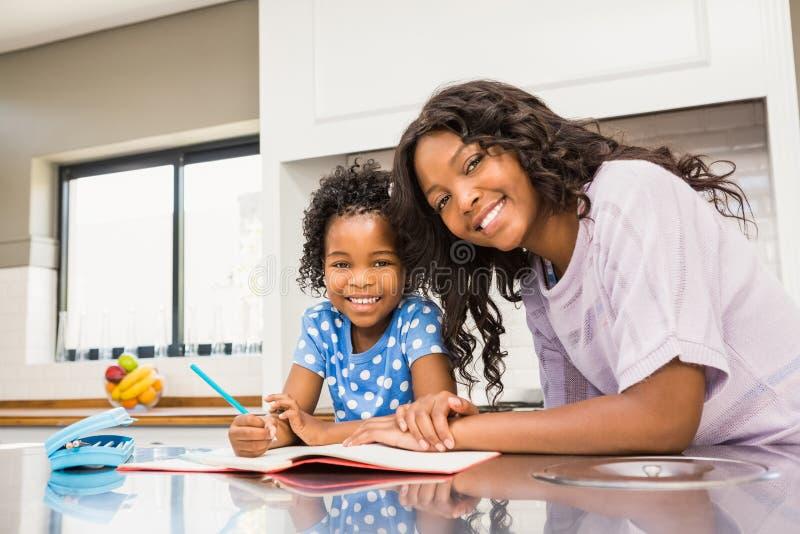 Jong meisje die haar thuiswerk met haar moeder doen royalty-vrije stock afbeeldingen