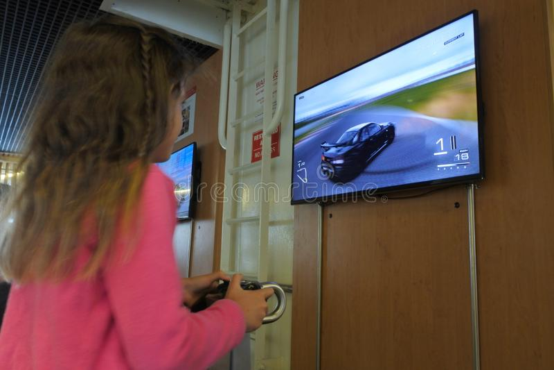 Jong meisje die het Auto rennen op Sony PlayStation spelen royalty-vrije stock afbeeldingen