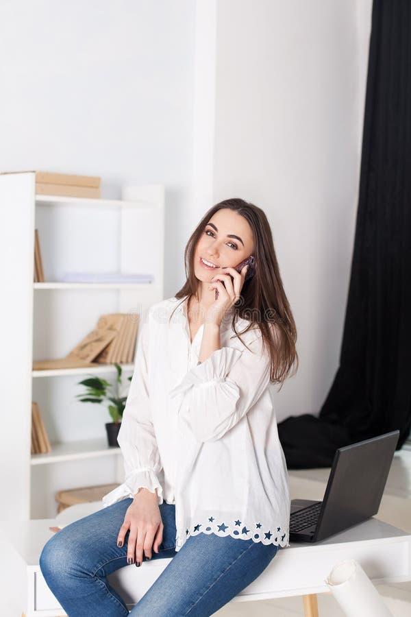 Jong meisje die in het bureau werken De meisjesvraag op de telefoon en zit op de lijst Het roepen van klanten van het bedrijf Zak stock afbeeldingen