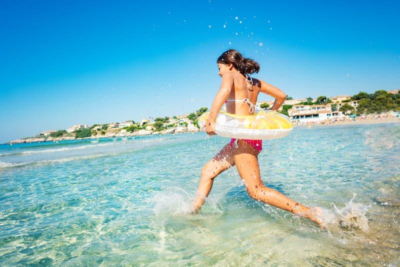 Jong meisje die het overzees met zwemmende buis tegenkomen stock foto