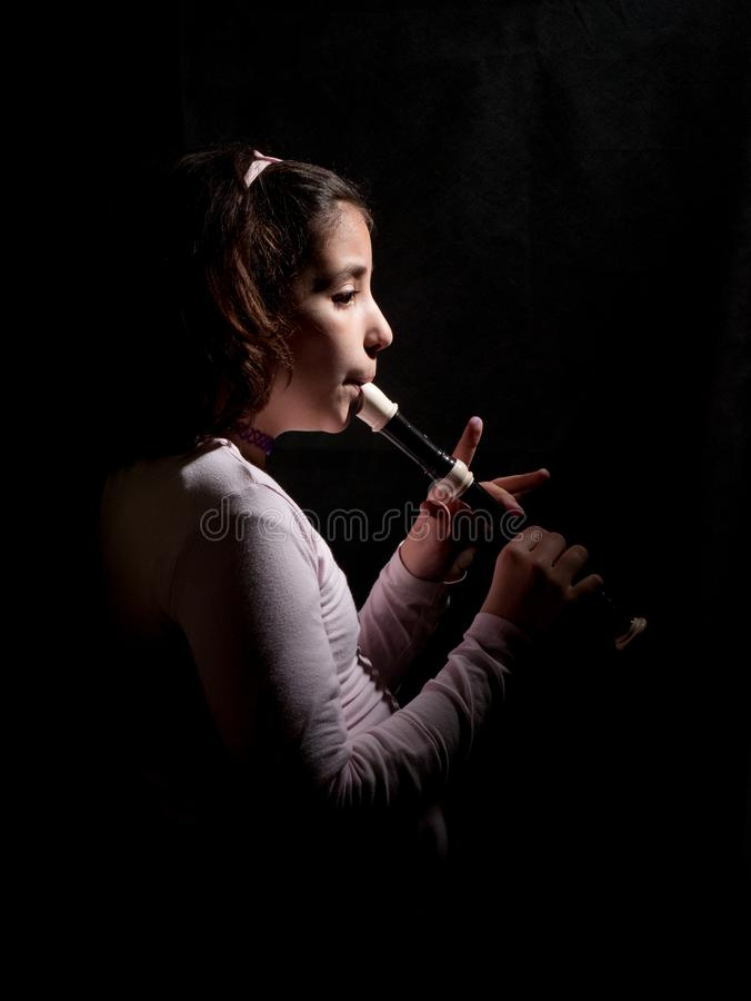 Jong meisje die het registreertoestel of de fluit spelen stock foto