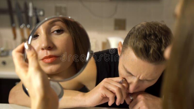 Jong meisje die kosmetische lippenstift, het bekijken een kleine spiegel dichtbij haar vriendzitting een lijst en het schrijven t royalty-vrije stock foto's