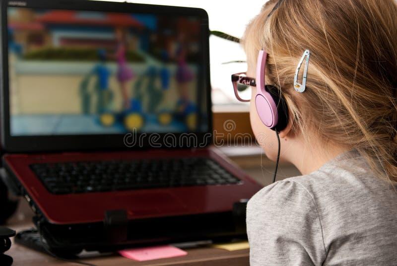 Jong meisje die laptop het scherm bekijken stock foto's