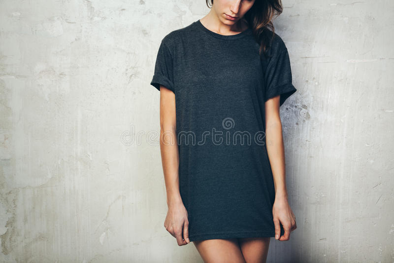 Jong meisje die lege zwarte t-shirt dragen Concrete muurachtergrond horizontaal stock afbeeldingen